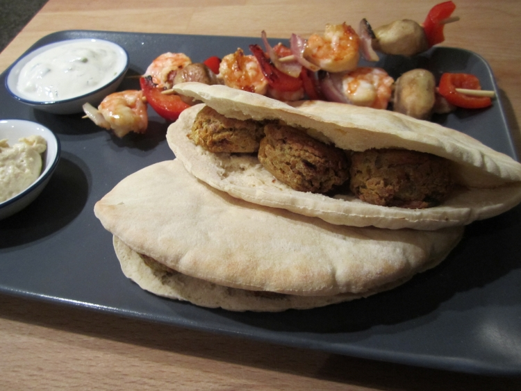 Falafel with pitta bread, tzatziki, hummous and griddled vegetable and prawn skewers